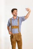Le jeune homme dans le pantalon en cuir prend un selfie avec son téléphone Photographie stock libre de droits