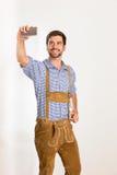 Le jeune homme dans le pantalon en cuir prend un selfie avec son téléphone Photographie stock