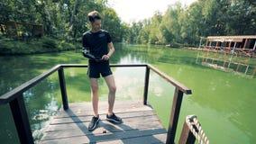 Le jeune homme dans les vêtements de sport avec un bras bionique robotique et un téléphone portable se tient sur un pont de riviè