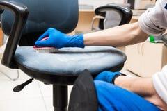 Le jeune homme dans les v?tements de travail et les gants en caoutchouc nettoie la chaise de bureau avec l'?quipement professionn photographie stock