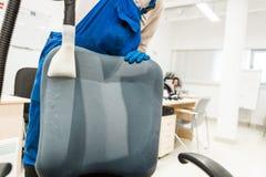 Le jeune homme dans les v?tements de travail et les gants en caoutchouc nettoie la chaise de bureau avec l'?quipement professionn images stock
