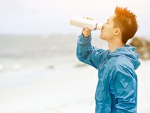 Le jeune homme dans le sport vêtx l'eau potable après séance d'entraînement sur la plage Image stock