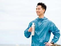 Le jeune homme dans le sport vêtx l'eau potable après séance d'entraînement sur la plage Photos libres de droits