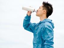 Le jeune homme dans le sport vêtx l'eau potable après séance d'entraînement sur la plage Photographie stock