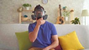 Le jeune homme dans un appartement moderne sent une mauvaise odeur et met dessus un respirateur banque de vidéos