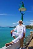 Le jeune homme dans un costume blanc s'assied sur le bord de mer Photos stock