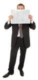 Le jeune homme dans un procès noir d'affaires affiche le newsp Photographie stock libre de droits