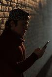 Le jeune homme dans une casquette de baseball tient le smartphone et le regarde image libre de droits