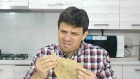 Le jeune homme dans une chemise de plaid mange un grand cheburek avec le dégoût et la nourriture de broches clips vidéos