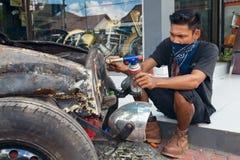 Le jeune homme de Balinese remplace la vieille voiture Photographie stock libre de droits