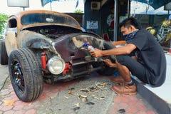 Le jeune homme de Balinese remplace la vieille voiture Photo libre de droits