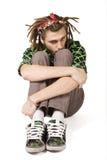 Le jeune homme de dreadlock s'assied d'isolement Photographie stock libre de droits