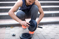 Le jeune homme de fintess prépare des dumbells pour la séance d'entraînement avec des poids Photos stock