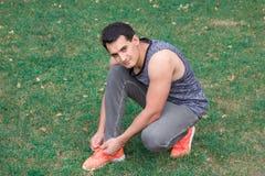 Le jeune homme de forme physique attache des lacets de chaussures sur ses espadrilles de sport Image libre de droits