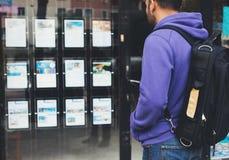Le jeune homme de hippie avec le sac à dos et la carte regardant l'hôtel d'affiche de promo d'annonce choisissent des apparteme image stock