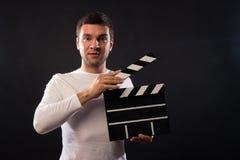 Le jeune homme de l'aspect caucasien tient une claquette Por photo libre de droits