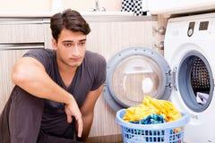 Le jeune homme de mari faisant la blanchisserie à la maison images libres de droits
