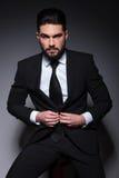 Le jeune homme de mode vous regarde et boutonne le costume photographie stock