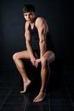 Le jeune homme de muscle s'assied sur un cube noir Photographie stock libre de droits