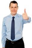 Le jeune homme de sourire avec des pouces lèvent le geste Image libre de droits