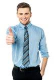 Le jeune homme de sourire avec des pouces lèvent le geste Photographie stock