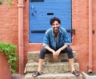 Le jeune homme de sourire avec la barbe et l'été façonnent des vêtements Photographie stock