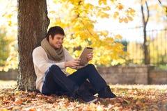 Le jeune homme de sourire avec le PC de comprimé en automne se garent Images stock