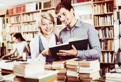 Le jeune homme de sourire et mûrissent la femme tenant des livres photographie stock libre de droits