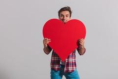 Le jeune homme de sourire se cache derrière un grand coeur rouge Photos stock