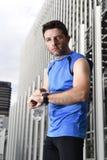 Le jeune homme de sport vérifiant le temps sur de chrono- coureurs de minuterie observent tenir la bouteille d'eau après stage de Photo stock