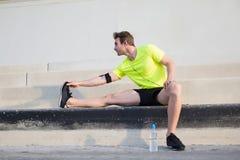 Le jeune homme de sports avertissant avant commencent son matin couru dehors au début de la matinée Image libre de droits
