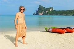 Le jeune homme de torse nu se tenant devant une rangée Kayaks des bateaux de canoës sur la plage de PhiPhi Don en Thaïlande photographie stock