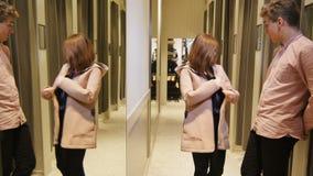Le jeune homme de vue de côté attend la fille essayant sur de nouveaux vêtements banque de vidéos