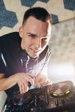 Le jeune homme DJ avec le mélangeur travaille Images stock