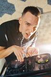 Le jeune homme DJ avec le mélangeur travaille Photo stock