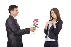 Le jeune homme donne une branche des fleurs à beau Image libre de droits