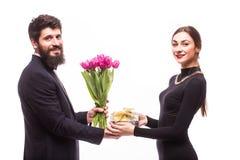 Le jeune homme donnent un cadeau pour son amie et les tulipes bucket Image libre de droits