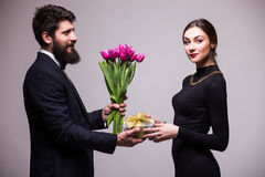 Le jeune homme donnent un cadeau pour son amie et les tulipes bucket Photographie stock