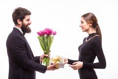 Le jeune homme donnent un cadeau pour son amie et les tulipes bucket Images stock