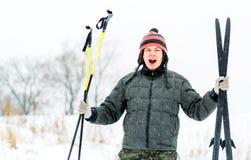 Le jeune homme drôle actif tient le ski, regardant l'appareil-photo et rire photographie stock libre de droits