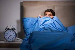 Le jeune homme effrayé dans le lit images libres de droits