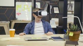 Le jeune homme emploie des verres de réalité virtuelle dans le bureau banque de vidéos