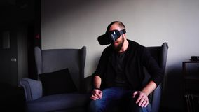 Le jeune homme employant des verres de VR amusés et traînant sur le tour sur l'attraction, s'assied dans la chaise en café élégan