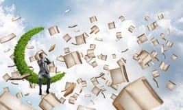Le jeune homme en ciel ne veulent voir rien et des livres qui volent autour Photos libres de droits
