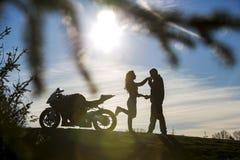 Le jeune homme en silhouette embrasse la main de son amie Photos libres de droits