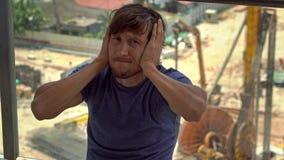 Le jeune homme en son appartement souffre du bruit produit par le chantier de construction en dehors de la fenêtre banque de vidéos
