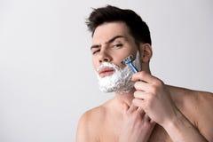 Le jeune homme enlève les cheveux non désirés de son visage Image stock