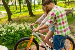 Le jeune homme enseigne son amie montant une bicyclette image stock