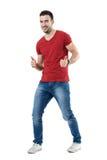 Le jeune homme enthousiaste gai dans le T-shirt rouge montrant des pouces lèvent le geste Photo stock