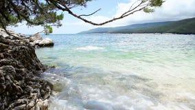 Le jeune homme entrent dans l'eau bleue de baie sur le rivage croate propre banque de vidéos